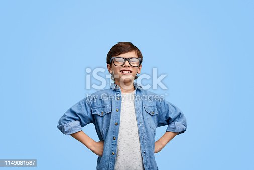Smart content kid holding hands on waist and smiling at camera against blue backdrop