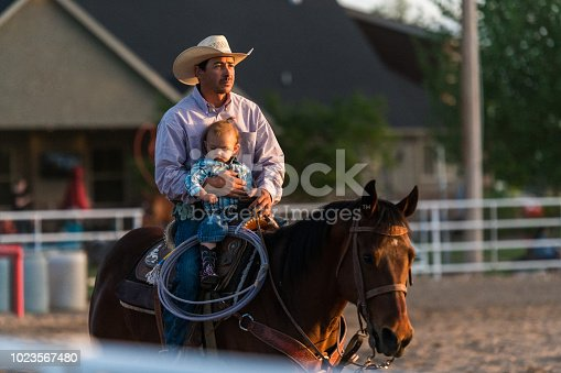Proud cowboy father with his young boy on a horse