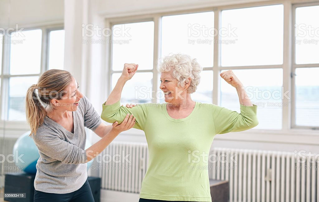 Proud elderly woman flexing her bicep with personal trainer stock photo