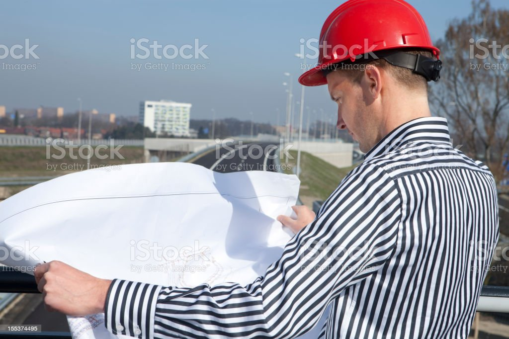 Proud engineer standing on bridge with blueprint royalty-free stock photo