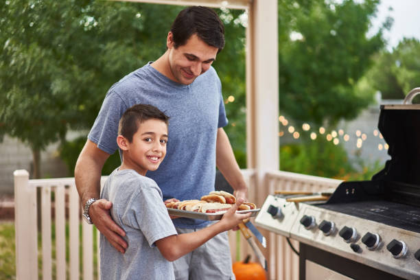 trotse vader en zoon tonen dienblad van gegrilde hotdogs foto