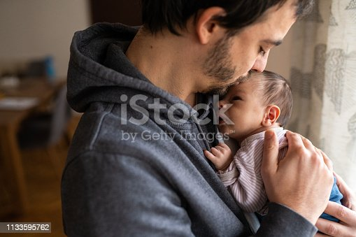 Young father holding newborn baby boy in arms, gently kissing baby boy in head