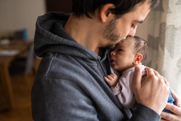 Stolzer Vater küsst Neugeborenen-Sohn – Foto
