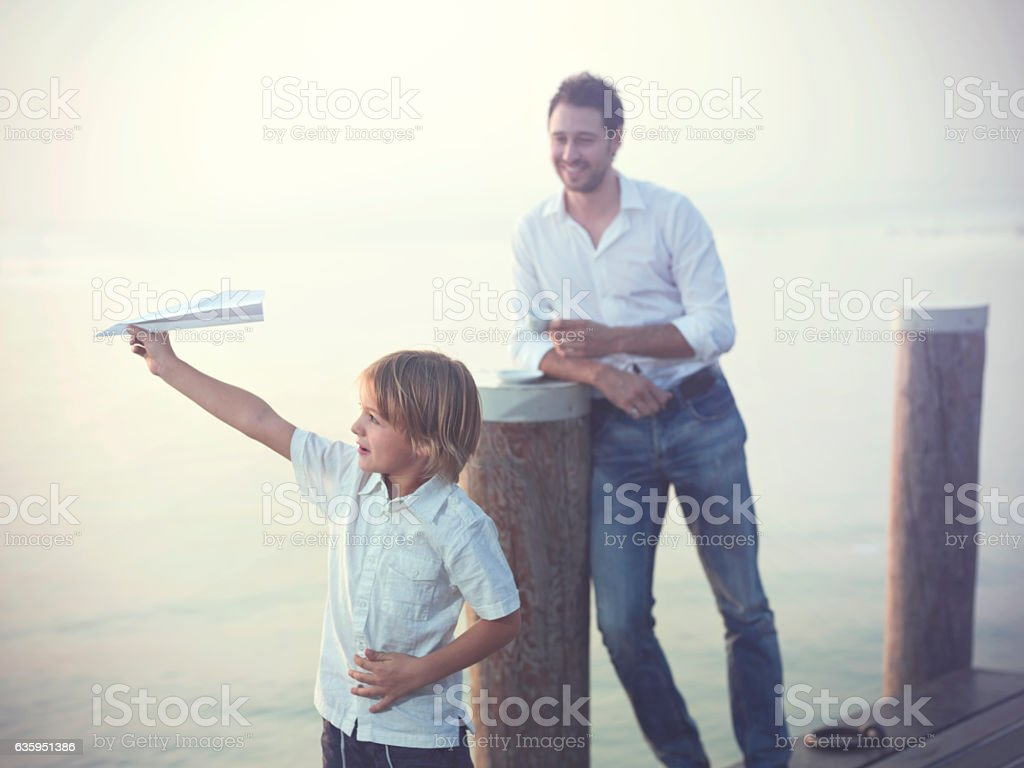 proud Father looks his son who is flying  paper airplane stock photo