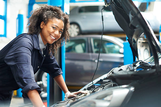 proud female auto mechanic A female mechanic is working under a bonnet of a car in a garage repair shop. She is wearing blue overalls.  She is looking proudly  to camera. vehicle hood stock pictures, royalty-free photos & images