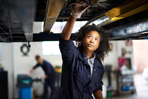 proud female garage mechanic . A young female adult mechanic is standing under a car in a garage. She is standing proudly and looking to camera mechanic stock pictures, royalty-free photos & images