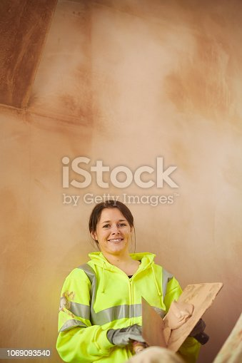 female plasterer tapping board joints before plastering