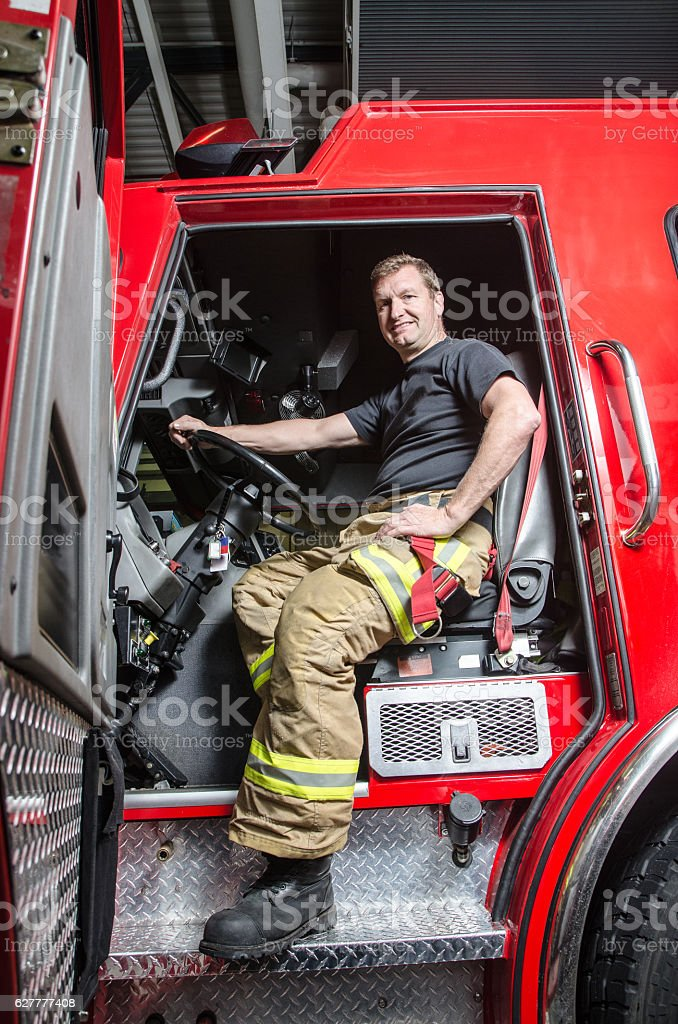 Proud fireman with protection pants sitting in truck stock photo