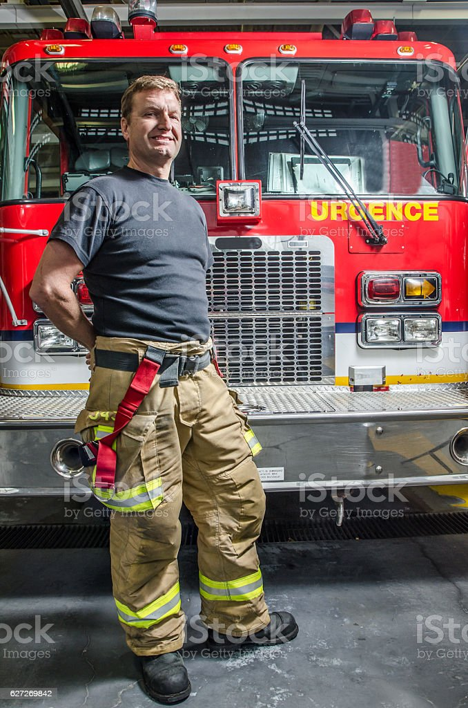 Proud fireman with protection pants standing in front of truck stock photo