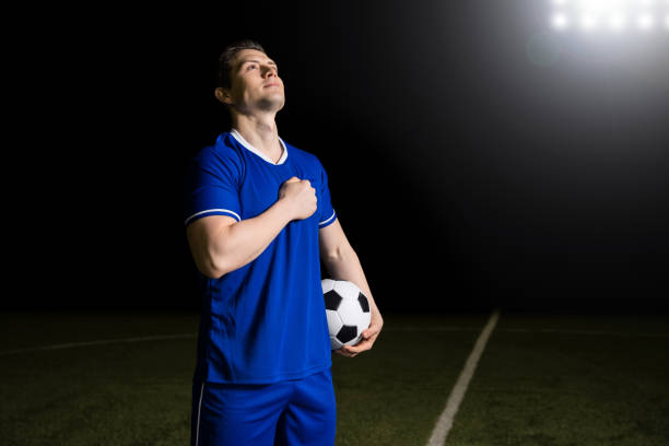 proud footballer listening to national anthem - national anthem stock photos and pictures