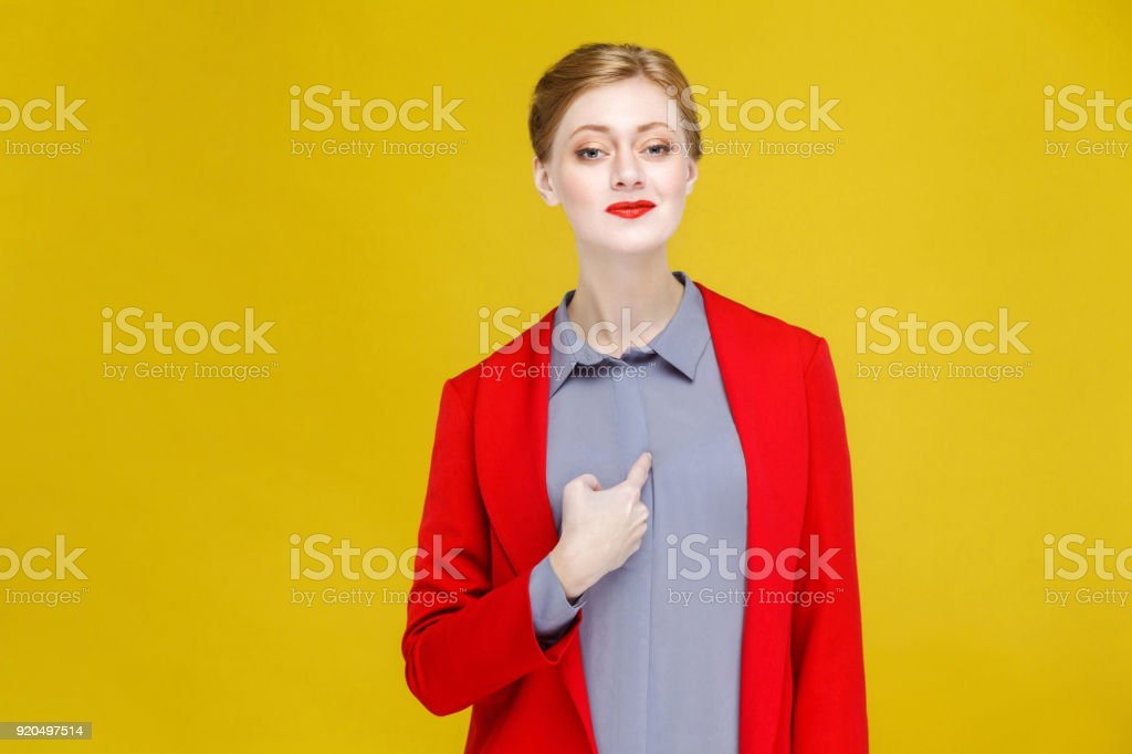 Proud ginger red head business woman in red suit pointing himself. stock photo