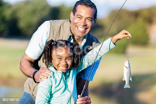 Cheerful African American girl smiles proudly while holding the fish she caught with her grandpa.