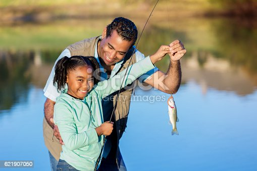 Pretty African American girls smiles while showing off a fish she caught with her grandpa. They are standing on the shore of a lake or pond.