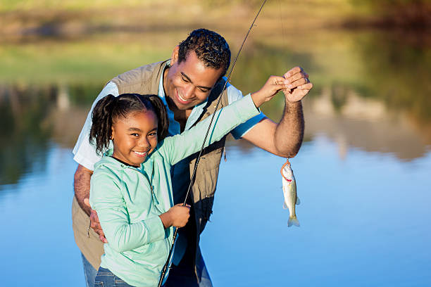proud girl shows off fish while fishing with granddad - fishing stock-fotos und bilder