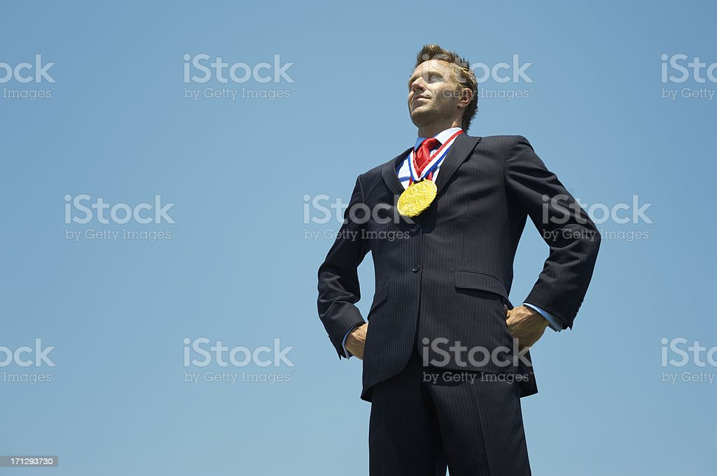 Proud Gold Medal Businessman Standing Outdoors with Hands on Hips royalty-free stock photo