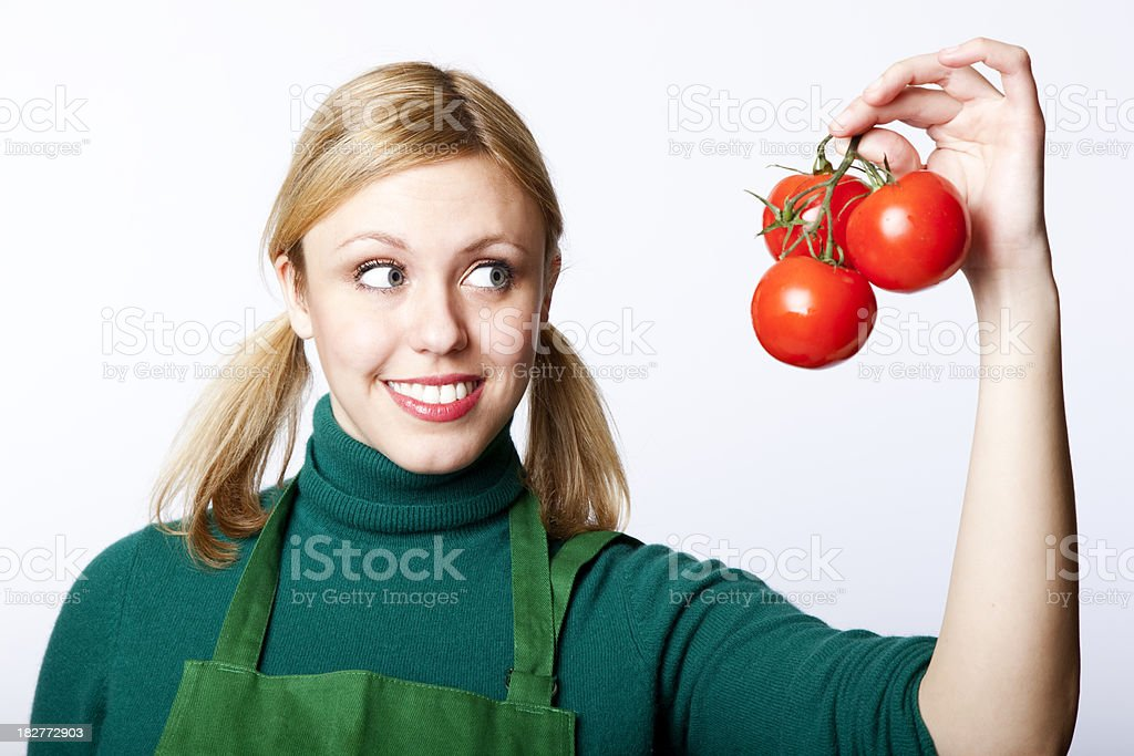 proud green grocer holding up organic tomatoes royalty-free stock photo
