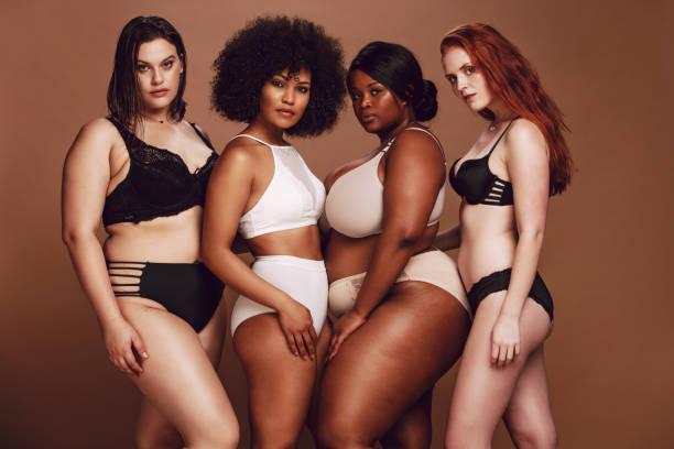 grupo orgulhoso de mulheres na roupa interior que levanta junto - body positive - fotografias e filmes do acervo