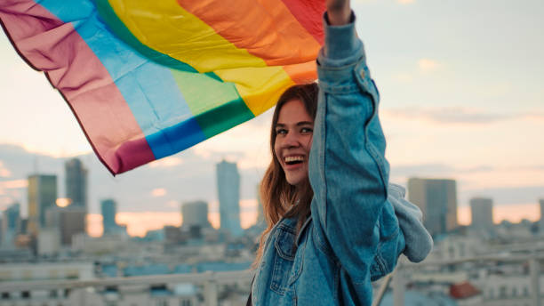 LGBT proud. Happy woman holding lgbt flag. Rooftop view stock photo