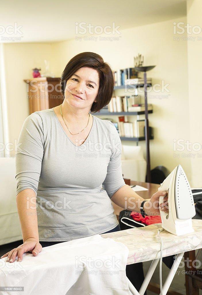 Proud homemaker posing at an ironing board royalty-free stock photo