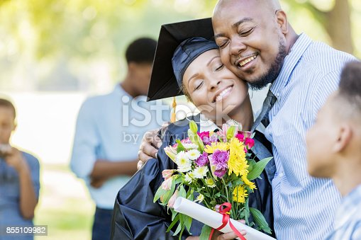 Proud husband gives his wife a bouquet of flowers on her graduation day. He is hugging her. She is holding the flowers and a diploma.