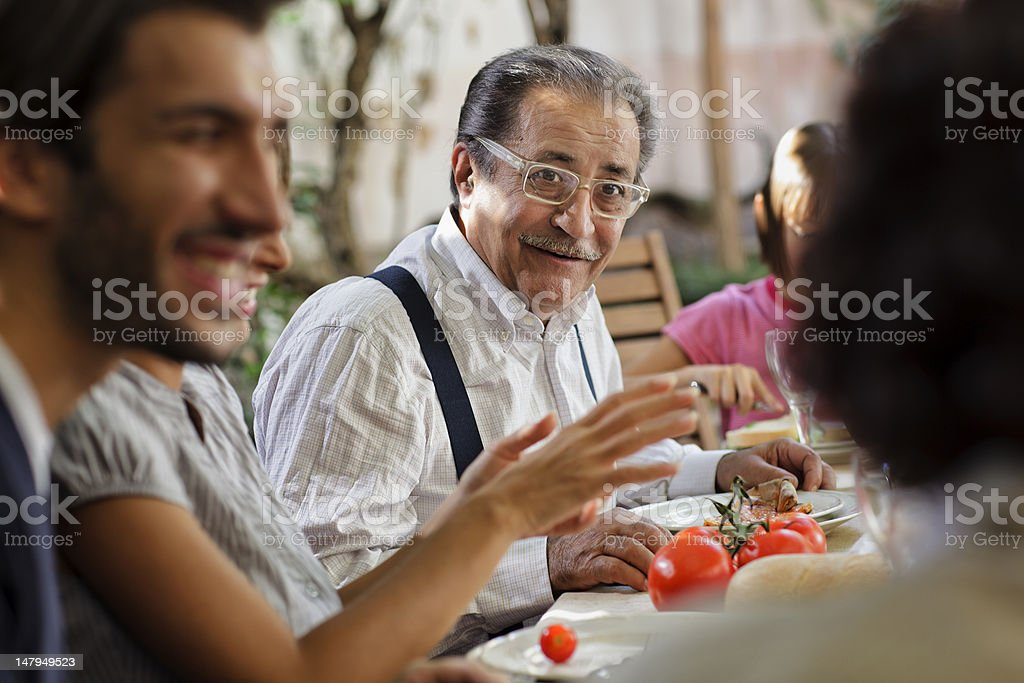 Proud Italian Grandfather having lunch with family stock photo