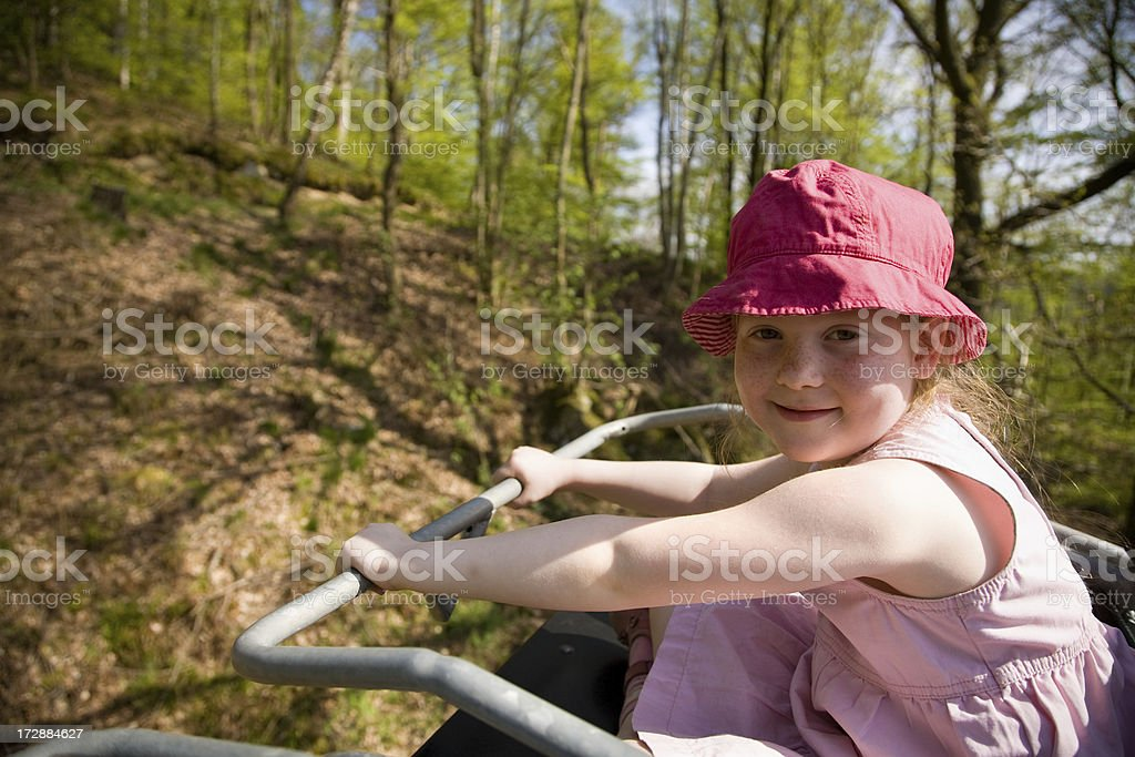 "Proud little girl in chairlift ""Young 5 year old girl with red hat, sitting proudly in a chairlift."" 4-5 Years Stock Photo"