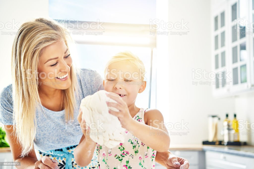 Proud little girl kneading the dough for her Mum stock photo