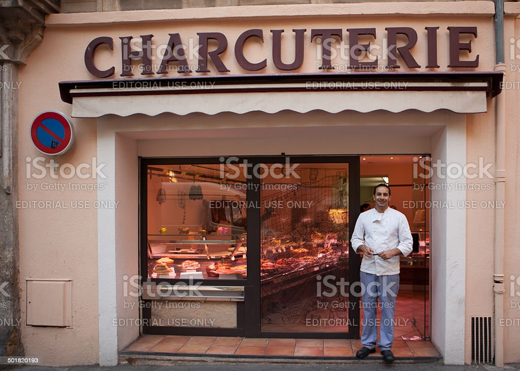 Proud man in front of a Charcuterie in France. royalty-free stock photo