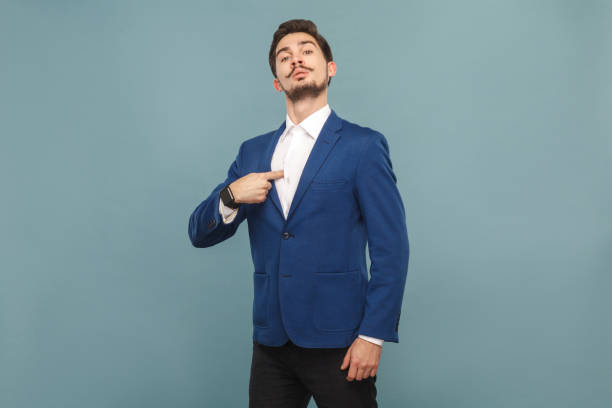Proud man pointing finger himself Proud man pointing finger himself. portrait of handsome bearded businessman in blue suit and white shirt, with smart watch. Indoor studio shot, isolated on light blue background arrogant stock pictures, royalty-free photos & images
