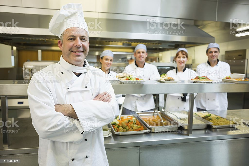 Proud mature head chef posing in a modern kitchen stock photo