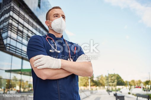Medical doctor in uniform standing in front of a medical building, hospital, wearing N95 protective face mask and surgical gloves during coronavirus, covid-19 epidemic.