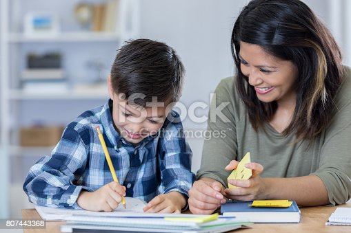 istock Proud mom encourages son as he does homework 807443368