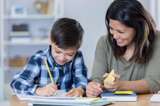Stolze Mama ermutigt Sohn, wie er Hausaufgaben macht – Foto