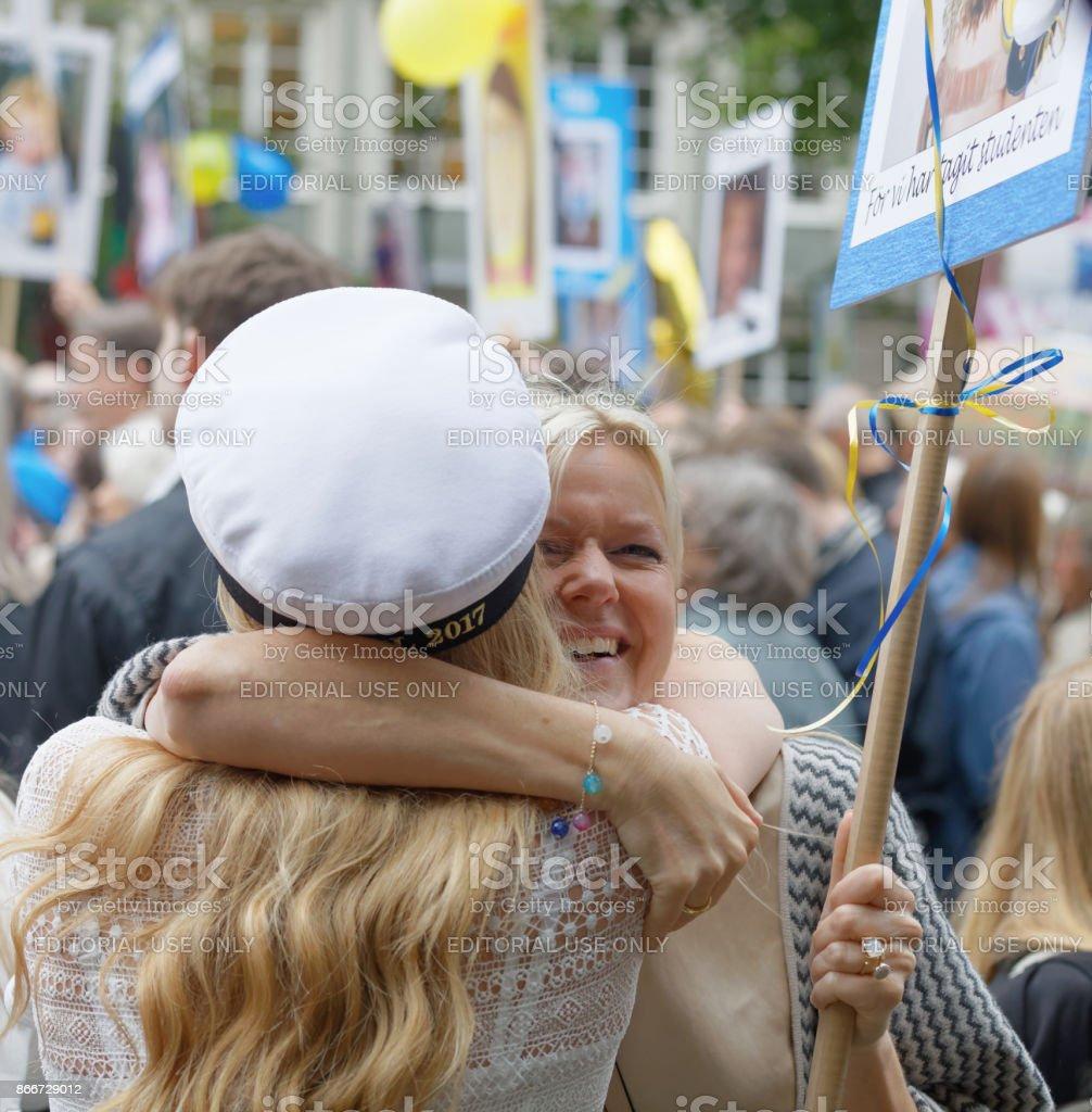Proud mother hugging her graduating granddaughter stock photo
