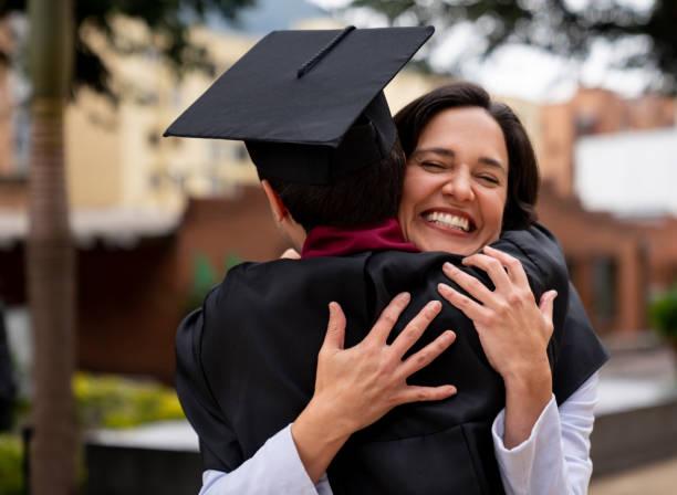 orgullosa madre abrazando a su hijo graduado - graduación fotografías e imágenes de stock