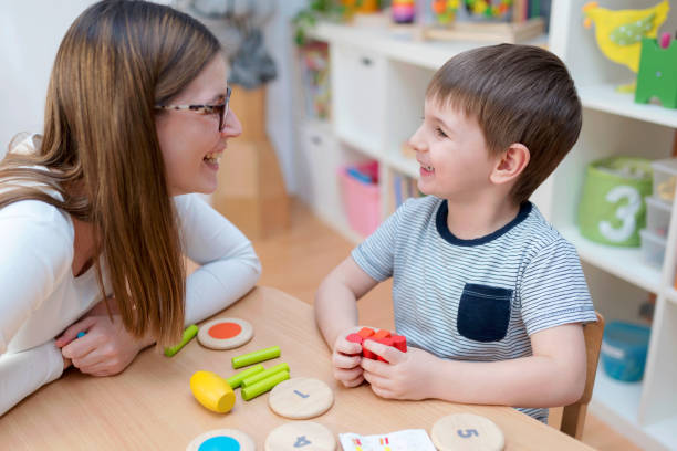 Proud mother looking at her son playing didactic games learning stock photo