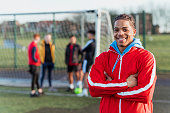 A portrait of a young mixed race man looking into the camera with his team mates in the background.