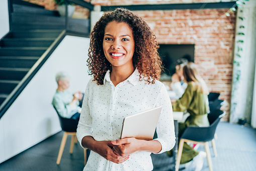 Shot of a beautiful smiling african-american businesswoman standing in front of her team and holding digital tablet. Portrait of successful businesswoman standing with her colleagues working in background. Multi-ethnic group of creative people on a business meeting in board room.