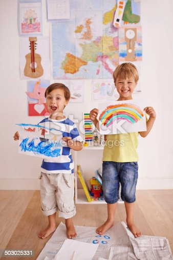 Portrait of two cute little boys holding up their artwork at home