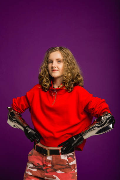 Proud of What She's Becoming One teenage girl with prosthetic arms standing infront of a coloured background. prosthetic hand stock pictures, royalty-free photos & images
