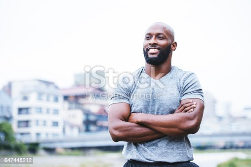 African - American man standing outdoors after his training in the city and smiling. He have his arms crossed and he is looking away.
