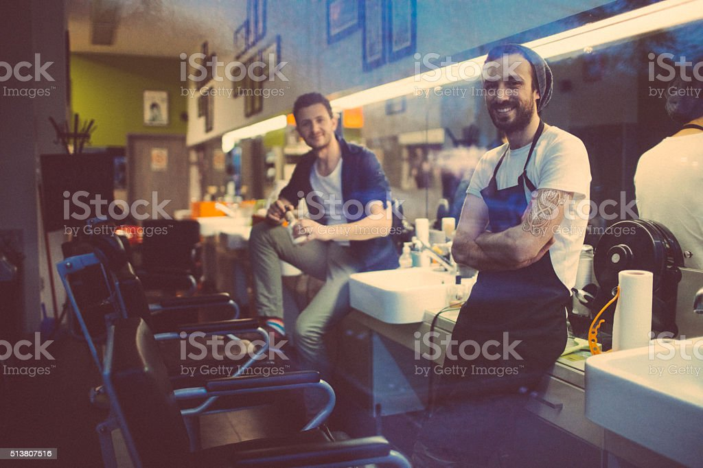 Proud owners of a small barber's shop stock photo