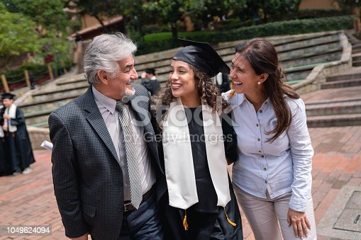 Portrait of a couple of proud parents hugging their daughter and celebrating her graduation - education concepts