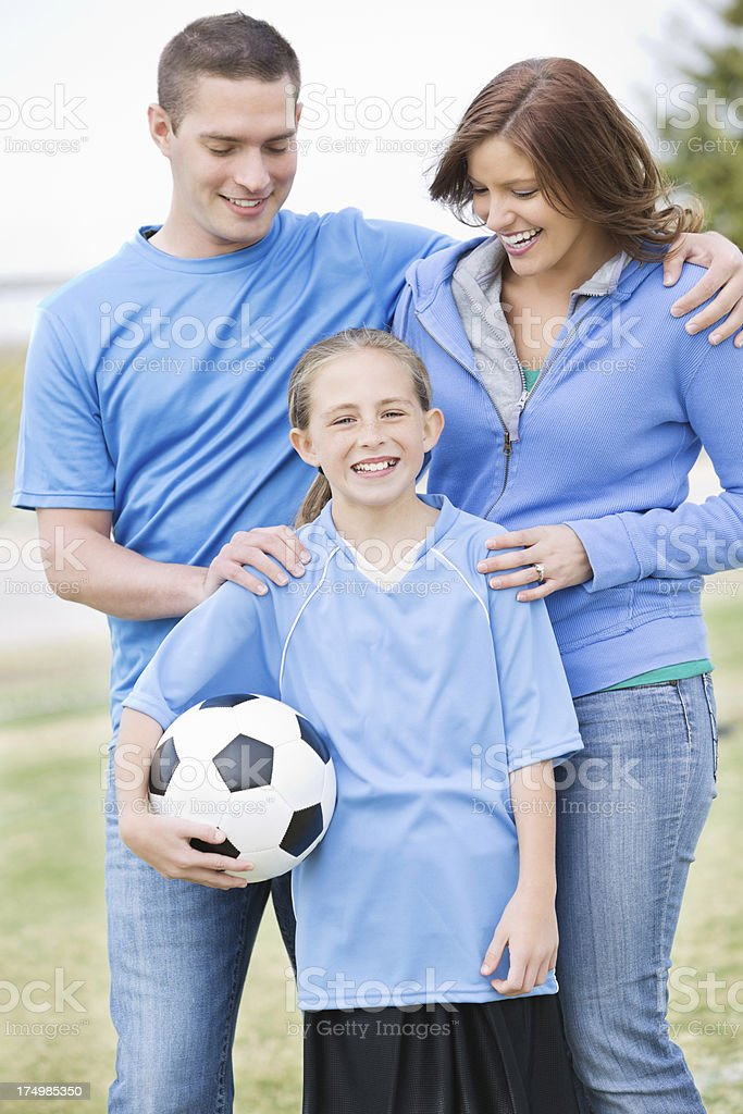 Proud parents with their young soccer playing daughter stock photo