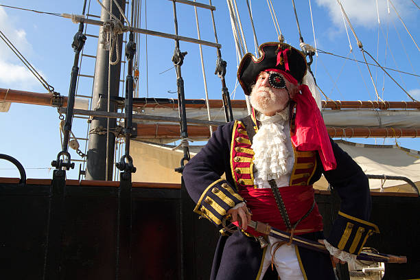Proud pirate with sailing ship Proud old pirate in colorful traditional costume stands on board ship and draws his sword. Schooner rigging and blue sky in background, horizontal layout with copy space. costume eye patch stock pictures, royalty-free photos & images