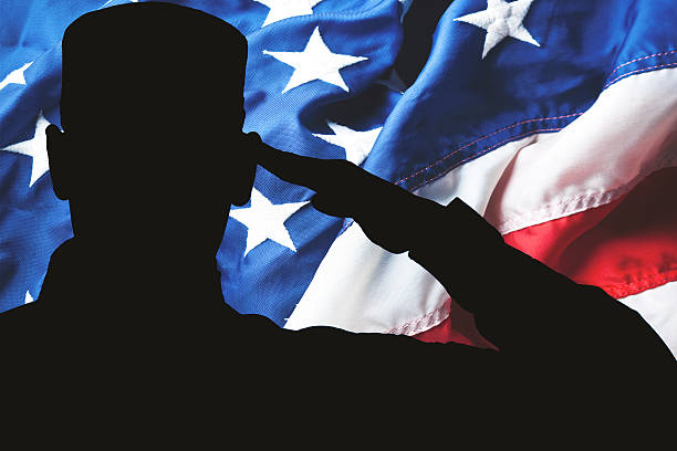 proud saluting male army soldier on american flag background - saluting stock photos and pictures