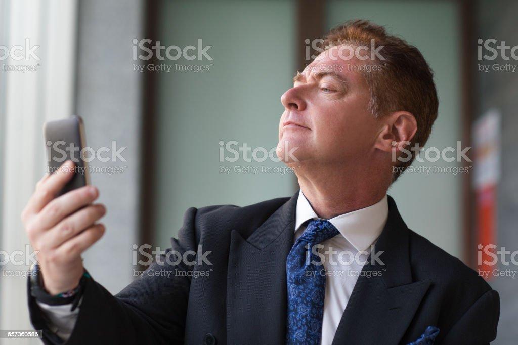 Empresario senior orgulloso teniendo selfie con teléfono - foto de stock