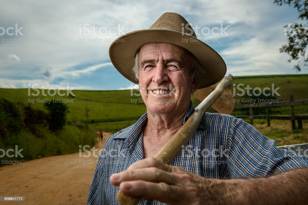 Proud senior farmer holding a hoe looking at camera, Brazil stock photo