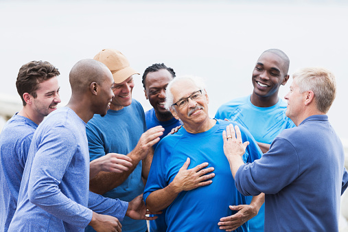 Multi-ethnic group of men of mixed ages wearing casual, blue shirts, outdoors.  Everyone is congratulating the senior Hispanic man (in his late 70s) wearing eyeglasses, patting him on the back.