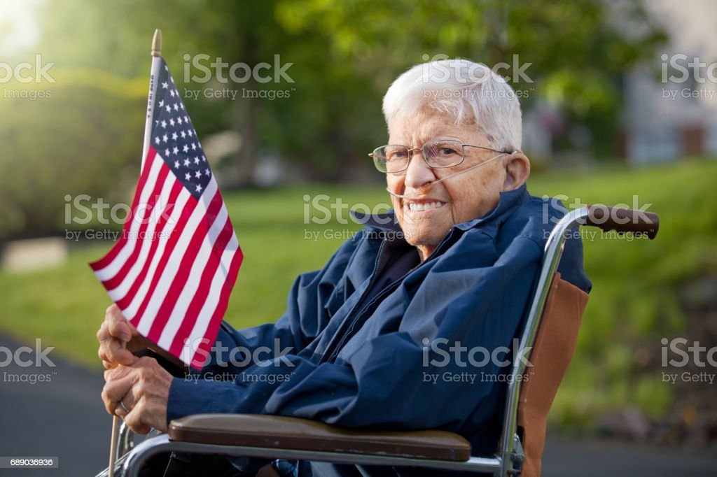 Proud Senior Man Veteran Holing US Flag A 92 year old World War II veteran sitting in his wheelcair outdoors holding an American flag. 90 Plus Years Stock Photo